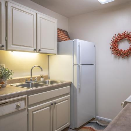 Kitchen with tile floors, beige cabinets, and white appliances.