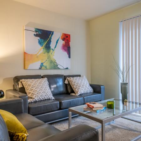 Carpeted living room with closed blinds, wall art, coffee table, two couches, and an end table with a lamp.