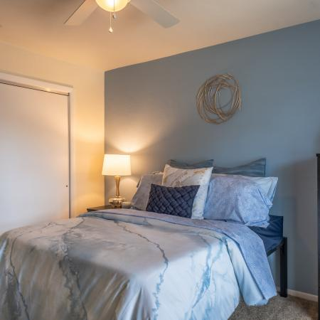 Carpeted bedroom with closet, blue accent wall, end table with lamp, drawer and window (out of view).