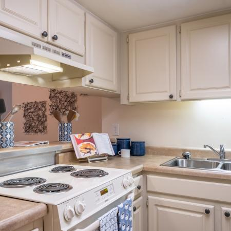 Kitchen with beige cabinets, stainless steel sink, white stove, lights under cabinets and a passthrough to the living room.