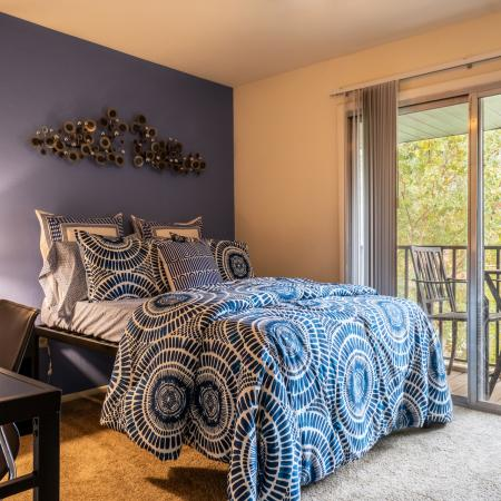 Carpeted bedroom with study desk and chair, end table with lamp, and access to a private balcony.