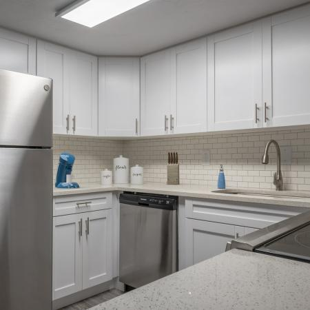 Kitchen with wood style floor, white cabinets, stainless steel appliances, white subway tile, white quartz countertops, a coffee machine and other items.