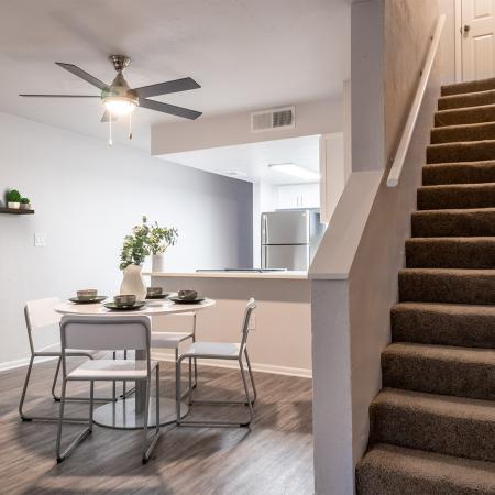 Apartment living and dining area with kitchen in the background, and staircase leading upstairs to the right. The dining set is circular with a white table and chair.