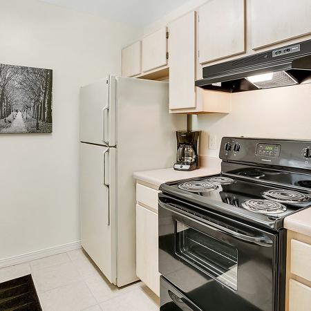 Tiled kitchen with black stove, white fridge, wooden cabinets, stainless steel sink, wall art, and a paper towel holder.