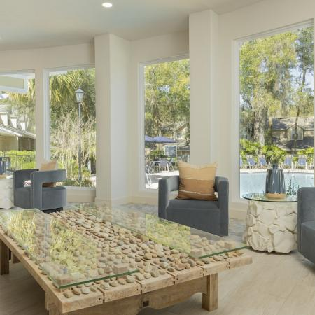 Large coffee table with wood, stones, and glass on top. There are large windows in the background facing the community pool.