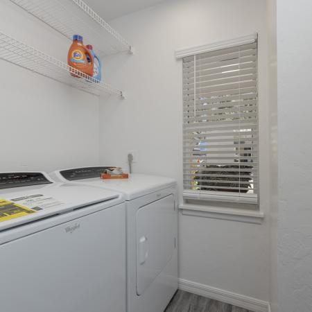 Laundry room with washer and dryer, hardwood floors, shelf space, and a window looking outside.