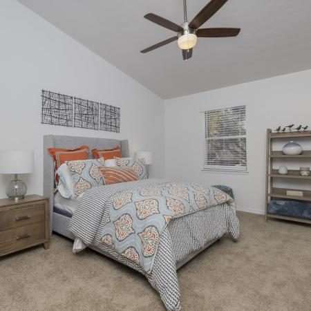 Carpeted bedroom with vaulted ceilings, ceiling fan, window, bed, end tables with lamps, drawers, and private bathroom.