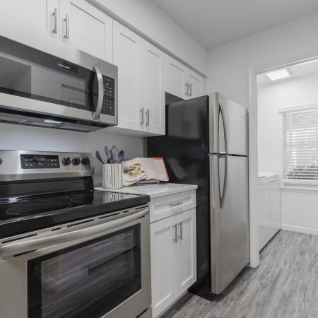 Kitchen with bar area, white quartz countertops, stainless steel appliances, white cabinets, and separate laundry room.