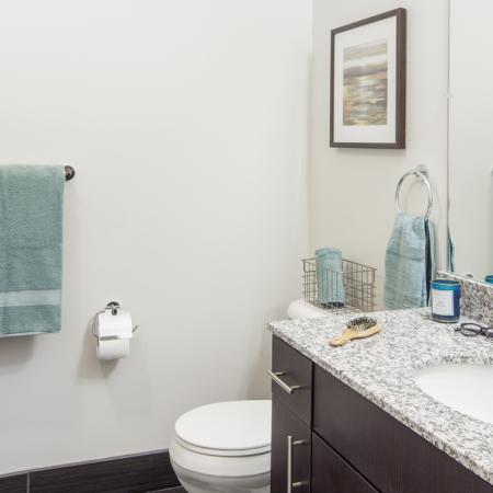 Spacious, luxury, modern bathroom with tile flooring, granite countertop