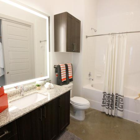 Modern Dallas Apartments | Second Bathroom with Soaking Tub, Backlit LED Mirror and Seasonal Closet located at our Dallas Texas apartments. (B2)