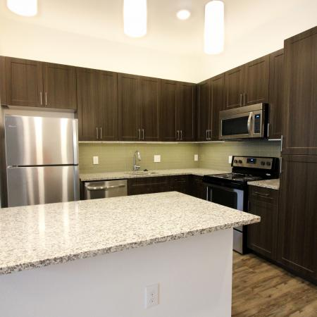 Modern Dallas Apartments | Apartment Kitchen with Quartz Counters and Specialty Light Fixtures in Dallas Texas.