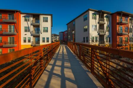 Modern Dallas Apartments | Walking on bridge towards our LBJ Station Ltd Dallas Texas apartments.