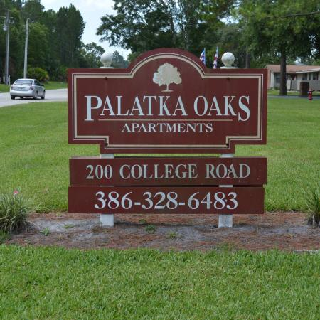 """Palatka Oaks Apartments, exterior, property sign, """"200 College Road 386-328-6483"""", grass, trees, street, buildings,"""