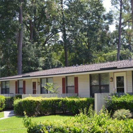 Bentwood Apartments, exterior, white siding, privacy fences, green grass, bushes, red shudders