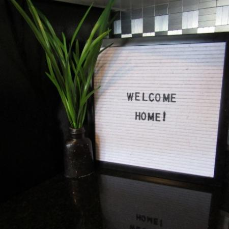 "Clubside Apartment Homes, interior, ""Welcome Home"" sign, plant"