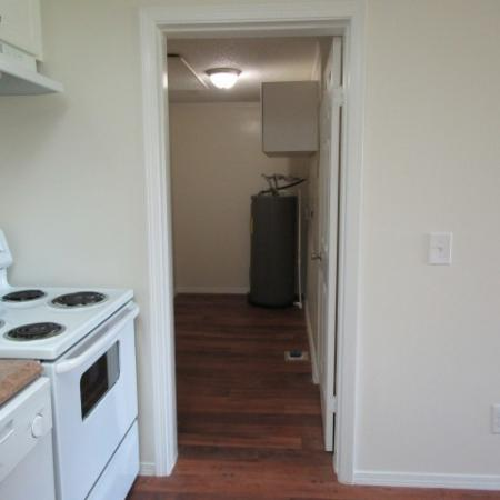 Clubside Apartment Homes, interior, kitchen, white stove and dishwasher, entrance to another room, wood floor