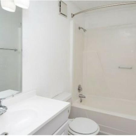 Bentwood Apartments, interior, bathroom, white, wood floor, shower/tub, sink, cabinet, toilet, mirror, towel rack