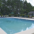 Overlook Gardens Exterior: Swimming pool with lounge chairs, surrounded by fence trees and building.
