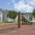 Overlook Gardens Exterior: Playground with swings, slide and jungle gym, surrounded by trees and apartments.