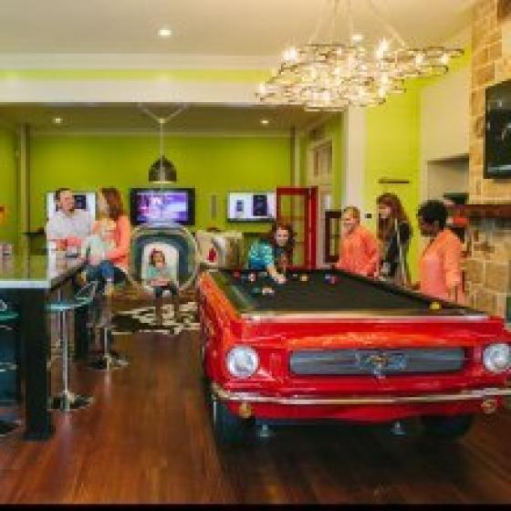 Fancy red car like pool table, Big screen TV, Bar Stools for seating