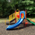 Outdoor Playground Structure: slide, climbers, playhouse, picnic table.