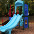 Outdoor Playground Structure: Double slide, climbers, playhouse, fenced.
