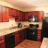 Black appliance package, Neutral colored counter-tops, wood-look laminate flooring, cherry cabinets.