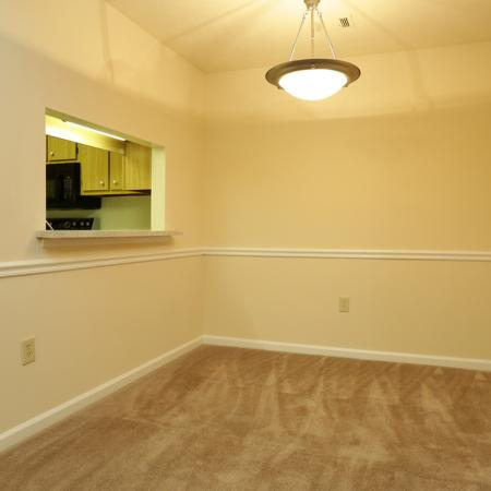 Cameron Crossing: brown carpet, white chair rail trim, open window looking into kitchen, globe hanging light fixture