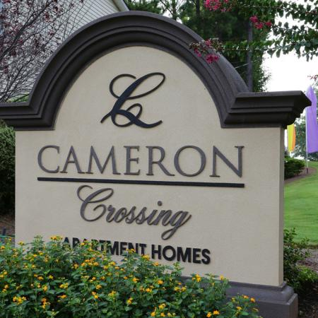 Cameron Crossing sign: gray stucco sign, landscaping