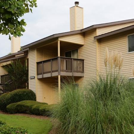 Cameron Crossing exterior: beige siding, balcony, well landscaped grounds