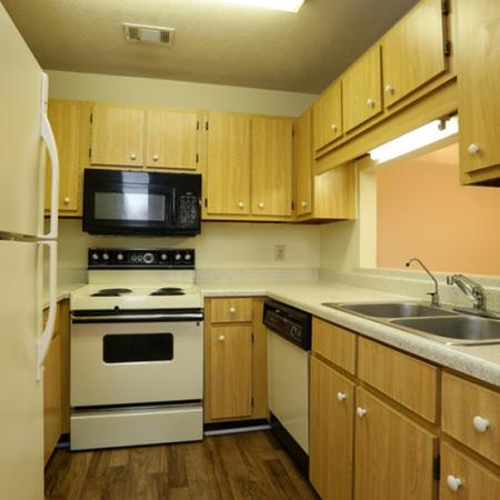 Cameron Crossing: kitchen, electric stoves, microwave above stove, dishwasher, wood flooring, oak cabinets with white pulls, refrigerator