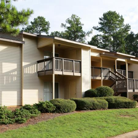Cameron Crossing exterior: beige siding, balconies and stair case, hedges and landscaping