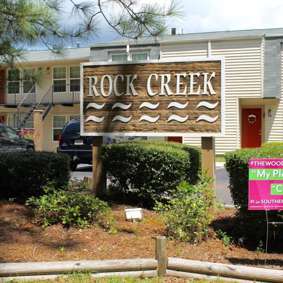 Rock Creek Exterior: Apartment community sign surrounded by shaded shrubbery, with 2 level Apartments in the background.