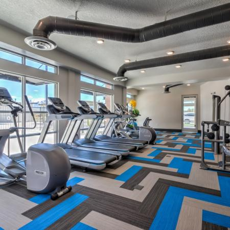 Residents Working Out at Fitness Center | Apartments For Rent West Jordan Utah | Novi at Jordan Valley Station