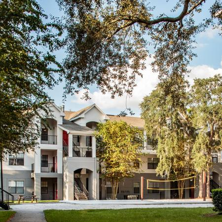 1800 The Ivy, exterior, white and gray buildings, three levels, balconies, palm trees, grass, volleyball court
