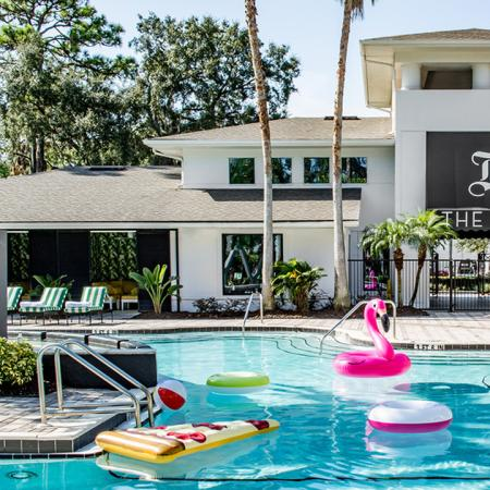 1800 The Ivy, exterior, sparkling blue swimming pool, club house entrance, lounge chairs, pink blow up flamingo, water toys, sign 'The Ivy' on side of gray and white building, trees,