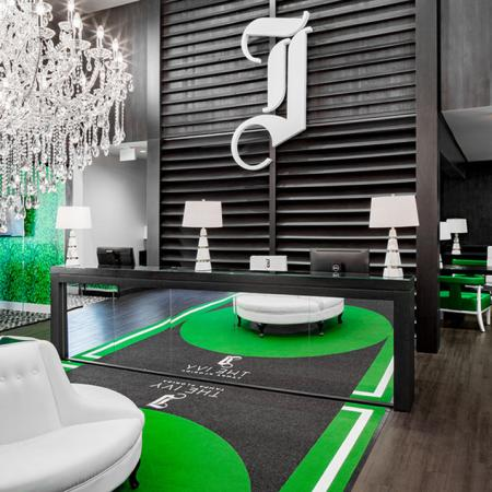 1800 The Ivy, interior, seating area, dark walls and floors, green accents, white circular sofa, mirrors, chandelier, windows, green doors, member service sign in next room, green chairs