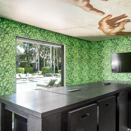1800 The Ivy, interior, black table and chairs, green leafy wall paper, tv, window to pool area