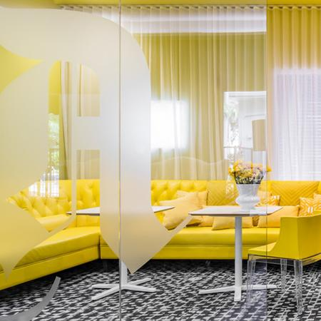 1800 The Ivy, interior, black and white carpet, large windows, glass doors, yellow walls and sectional
