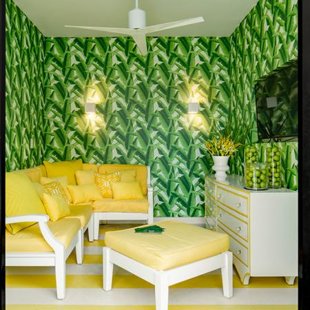 1800 The Ivy, interior, tv room, yellow and white sofa, ottoman, dresser, tv, green foliage wall paper