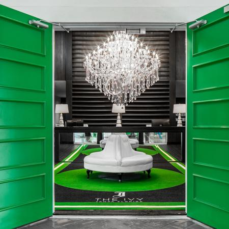 1800 The Ivy, interior, seating area, dark walls and floors, green accents, white circular sofa, mirrors, chandelier, windows, green doors