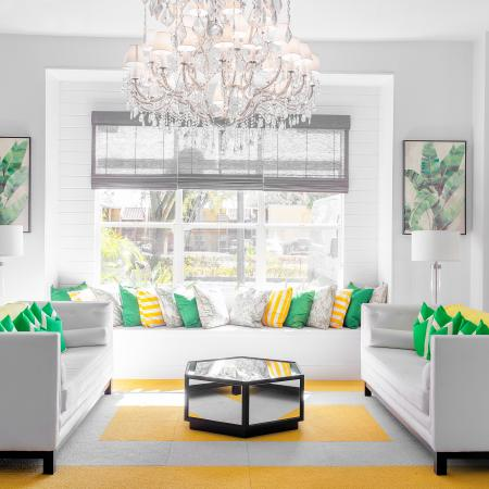 1810 The Social, interior, spacious seating area, chandelier, decor is white with green and yellow accents, three large sofas, large window