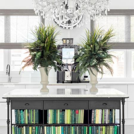 1810 The Social, interior, white wall, windows, white floor, chandelier, potted plants, coffee maker, table with books on bottom shelves, green tones