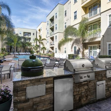 1802 4050Lofts, exterior, out door kitchen with grills, lounge chairs, pool, palm trees, balconies, courtyard, green and tan building exterior,