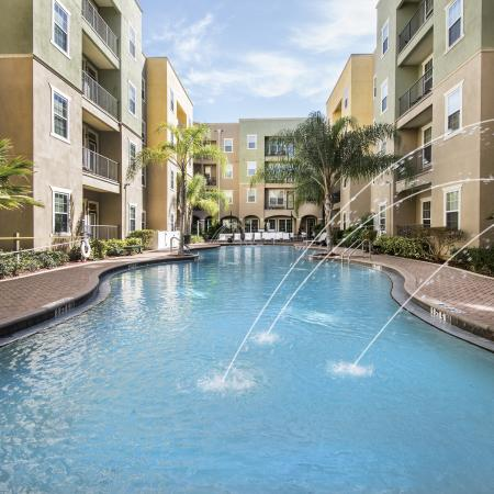 1802 4050Lofts, exterior, sparkling blue swimming pool, fountains, stone walkways, palm trees, courtyard, tan and green building exteriors
