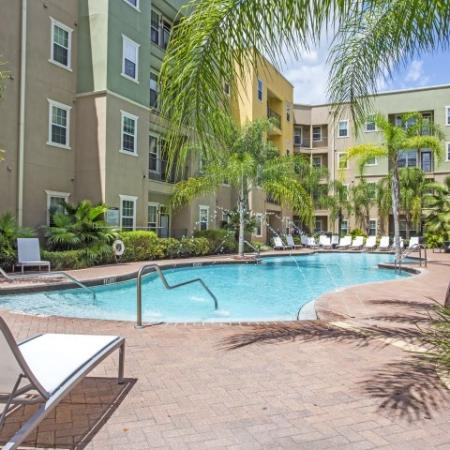 1802 4050Lofts, exterior, lounge chairs, pool, palm trees, balconies, courtyard, green and tan building exterior,