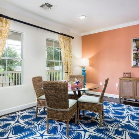 Cabana West Apartments interior: clubhouse area with chairs, table, and two windows