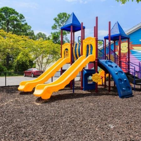 Cabana West Apartments exterior: playground with various slides and climbing features