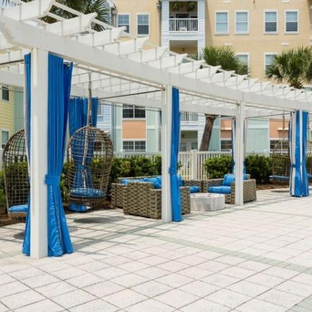 Cabana West Apartments exterior: relaxation area with chairs and shade by the pool