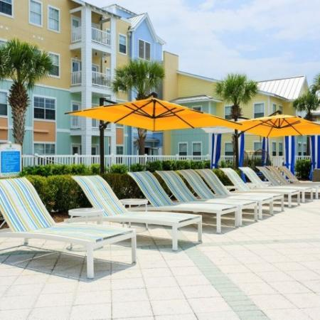 Cabana West Apartments exterior: beach chairs and umbrellas on the poolside
